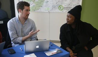 David Bransfield, a state outreach coordinator for Young Invincibles, a group which supports President Barack Obama's health care law, talks with student Philippe Komongnan, 27, who is in the process of signing up for health care, at the University of the District of Columbia in Washington, Thursday, Jan. 30, 2014. An army of workers and volunteers has fanned out around the country trying to enroll young and healthy people in health insurance now available through Obama's signature law. (AP Photo/Charles Dharapak)