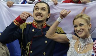 Tatiana Volosozhar and Maxim Trankov of Russia gesture to spectators as they wait for their results in the team pairs short program figure skating competition at the Iceberg Skating Palace during the 2014 Winter Olympics, Thursday, Feb. 6, 2014, in Sochi, Russia. (AP Photo/Darron Cummings, Pool)