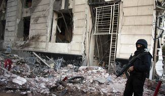 In this file photo taken Tuesday, Dec. 24, 2013, an Egyptian policeman guards the scene of an explosion at a police headquarters building that killed at least a dozen people, wounded more than 100, and left scores buried under the rubble, in the Nile Delta city of Mansoura, 110 kilometers (70 miles) north of Cairo, Egypt. The militant group Ansar Beit al-Maqdis, which has waged a campaign of bombings and assassinations for months in Egypt, has quickly advanced in weaponry and sophistication of attacks, drawing on the experience of Egyptians who fought in Syria. (AP Photo/Ahmed Ashraf, File)