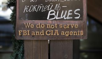 "A sign that says ""We do not serve FBI and CIA agents,"" hangs outside a restaurant on the opening day of the 2014 Winter Olympics, Friday, Feb. 7, 2014, in Krasnaya Polyana, Russia. (AP Photo/Jae C. Hong)"