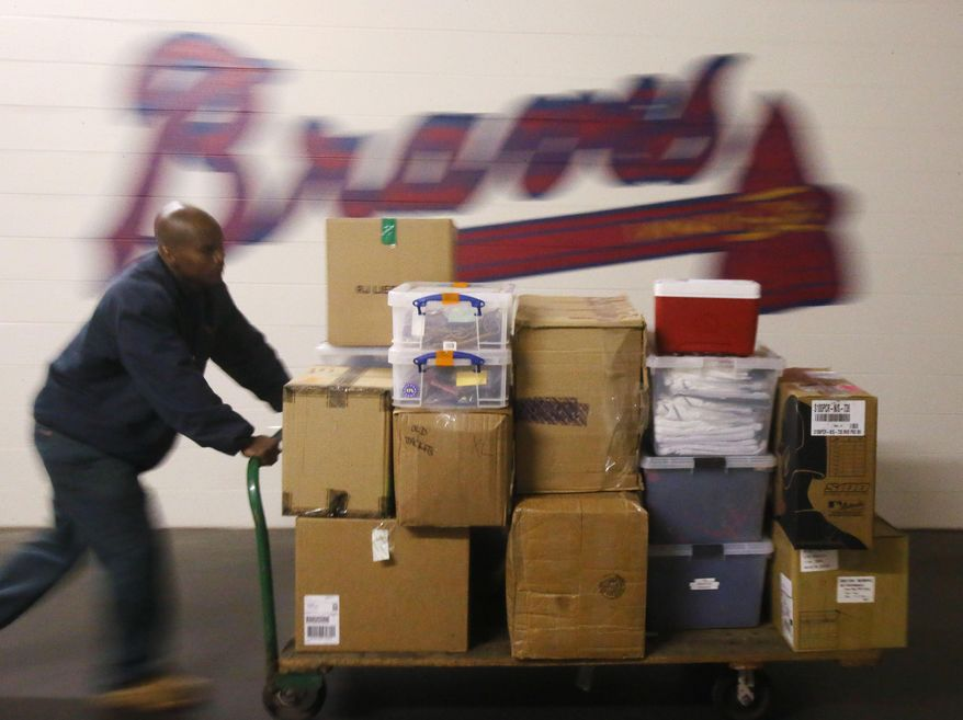 Dannan Edison, from Atlanta Peach Movers, helps pack and load Atlanta Braves baseball equipment for the trip south for spring training Friday, Feb. 7, 2014, in Atlanta. (AP Photo/Atlanta Journal-Constitution, Bob Andres)  MARIETTA DAILY OUT; GWINNETT DAILY POST OUT; LOCAL TV OUT; WXIA-TV OUT; WGCL-TV OUT