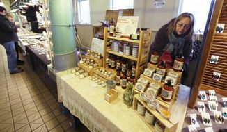 ** FILE ** Maija Szymanowski works at a stand at Pike Place Market Thursday, Feb. 6, 2014 in Seattle that sells body-care products including lotions, salves, and serums made in Washington state with hemp that is grown in Canada. With recreational marijuana use now legal in Washington, state legislators are discussing whether the state should also launch an industrial hemp industry. (AP Photo/Ted S. Warren)