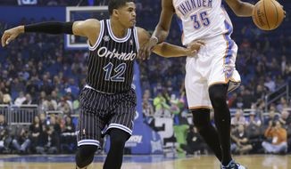 Oklahoma City Thunder's Kevin Durant (35) makes a move to get around Orlando Magic's Tobias Harris (12) during the first half of an NBA basketball game in Orlando, Fla., Friday, Feb. 7, 2014. (AP Photo/John Raoux)
