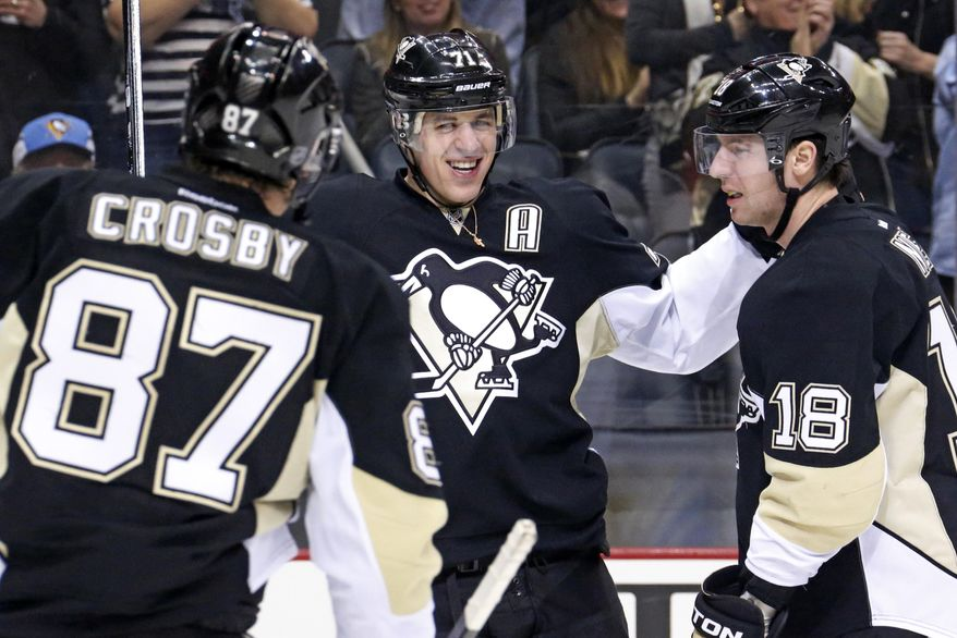 Pittsburgh Penguins' Evgeni Malkin (71) celebrates his goal with James Neal (18), and Sidney Crosby (87) during the second period of an NHL hockey game against the New York Rangers in Pittsburgh, Friday, Feb. 7, 2014. (AP Photo/Gene J. Puskar)