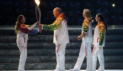 Russian wrestler Alexander Karelin, second from left, hands the torch to Russian gymnast Alina Kabaeva, left,  as Russian tennis player Maria Sharapova, second from right, and Russian pole vaulter Yelena Isinbayeva look on during the opening ceremony of the 2014 Winter Olympics in Sochi, Russia, Friday, Feb. 7, 2014. (AP Photo/Mark Humphrey)