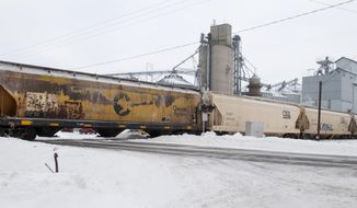 A train blocks Gera Road south of Bradley in Frankenmuth Township, Mich.,  Friday, Feb. 7, 2014.   Authorities say the train got stuck in snow,  blocking traffic at an area crossing. A portion of M-83 in Saginaw County was closed Friday morning about 75 miles northwest of Detroit. The Michigan Department of Transportation is asking motorists to use a detour. Southern Michigan got up to 8 inches of fresh snow on Tuesday and Wednesday. Blowing snow and ice have caused continued problems. (AP Photo/The Saginaw News, Jeff Schrier) ALL LOCAL TV OUT; LOCAL TV INTERNET OUT