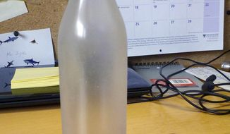 This January 2014 photo released by the Woods Hole Oceanographic Institution on Cape Cod, Massachusetts, shows a glass bottle that had contained a message from the institution, which was recovered on Sable Island, Nova Scotia, by biologist Warren N. Joyce of Canada's Department of Fisheries and Oceans. The bottle  was among thousands dumped in the Atlantic Ocean between 1956 and 1972 as part of a program by Woods Hole oceanographer Dean Bumpus to study surface and bottom currents. About 10 percent of the 300,000 drift bottles have been found over the years. (AP Photo/Warren N. Joyce)