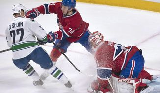 Montreal Canadiens goaltender Carey Price makes a save against Vancouver Canucks' Daniel Sedin as Canadiens' Alexei Emelin defends during the third period of an NHL hockey game Thursday, Feb. 6, 2014, in Montreal. (AP Photo/The Canadian Press, Graham Hughes)