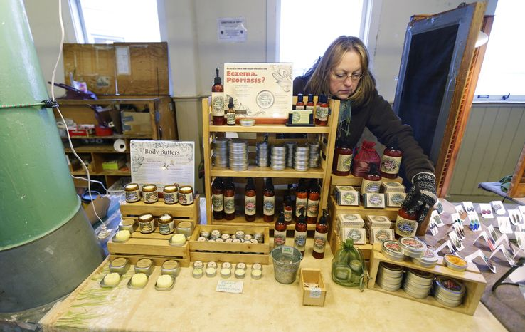 Maija Szymanowski works at a stand at Pike Place Market Thursday, Feb. 6, 2014 in Seattle that sells body-care products including lotions, salves, and serums made in Washington state with hemp that is grown in Canada. With recreational marijuana use now legal in Washington, state legislators are discussing whether the state should also launch an industrial hemp industry. (AP Photo/Ted S. Warren)