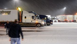 Truck drivers walk in and out of Love's Travel Stop in Napavine, Wash. on Thursday, Feb. 6, 2014. Several inches of snow blanketed Southwest Washington state on Thursday forcing some semi-truck drivers to stop for the night. (AP Photo/The Chronicle, Pete Caster)