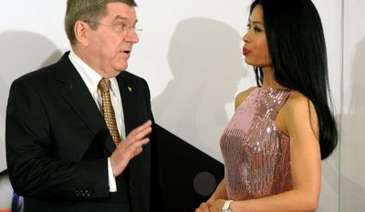 International Olympic Committee President Thomas Bach, left, chats with former musician Vanessa-Mae, who will compete for Thailand as alpine skier Vanessa Vanakorn before the IOC President's Gala Dinner on the eve of the opening ceremony of the 2014 Winter Olympics, Thursday, Feb. 6, 2014, in Sochi, Russia.  (AP Photo/Andrej Isakovic, Pool)