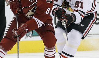 Phoenix Coyotes' Keith Yandle (3) tries to keep the puck away from Chicago Blackhawks' Marian Hossa (81) during the first period in an NHL hockey game, Friday Feb. 7, 2014, in Glendale, Ariz. (AP Photo/Ross D. Franklin)