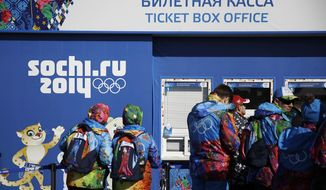 Workers line up outside a ticket box office on the Olympic Plaza ahead of the upcoming 2014 Winter Olympics, Thursday, Feb. 6, 2014, in Sochi, Russia. (AP Photo/David Goldman)