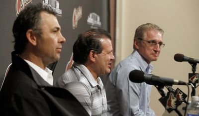 """Members of the gold medal 1980 """"Miracle on Ice"""" U.S. hockey team, Neal Broten, left, Mike Eruzione and Buzz Scheider, right, talk to the media prior to being honored at an NHL hockey game between the Chicago Blackhawks and the Phoenix Coyotes, Friday Feb. 7, 2014, in Glendale, Ariz. (AP Photo/Ross D. Franklin)"""