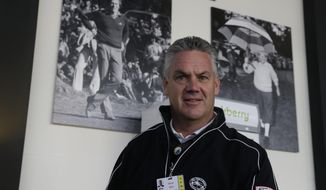 Steve John, CEO of the Monterey Peninsula Foundation and tournament director of the AT&T Pebble Beach Pro-Am golf tournament, poses beneath photographs of Clint Eastwood, left, and Bing Crosby, right, Friday, Feb. 7, 2014, in Pebble Beach, Calif. John was choking on a piece of cheese at a volunteer party when Eastwood gave him the Heimlech maneuver, Wednesday evening, Feb. 5, 2014, at the Monterey Conference center in Monterey, Calif. (AP Photo/Eric Risberg)