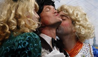 Actor Neil Patrick Harris is kissed by actors in drag during his roast as Man of The Year by Harvard University's Hasty Pudding Theatricals in Cambridge, Mass., Friday, Feb. 7, 2014. (AP Photo/Elise Amendola)