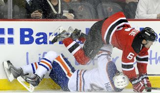 New Jersey Devils' Andy Greene (6) checks Edmonton Oilers' Taylor Hall to the ice during the first period of an NHL hockey game on Friday, Feb. 7, 2014, in Newark, N.J. (AP Photo/Bill Kostroun)