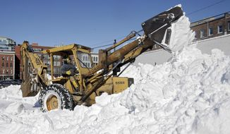 Sam Rendina plows snow into a large pile in the corner of a parking lot in Cleveland Friday, Feb. 7, 2014. Cities across Ohio were still cleaning up after the storm that dumped 6-10 inches of snow Tuesday night and Wednesday. (AP Photo/Mark Duncan)