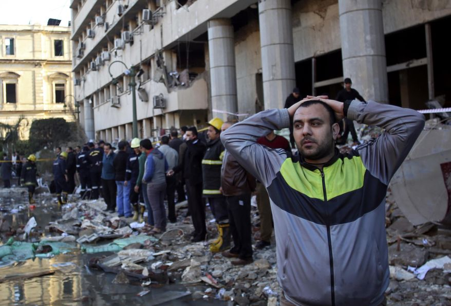 FILE - I this file photo taken Friday, Jan. 24, 2014, an Egyptian man stands in the rubble after an explosion at the Egyptian police headquarters in downtown Cairo. The militant group Ansar Beit al-Maqdis, which has waged a campaign of bombings and assassinations for months in Egypt, has quickly advanced in weaponry and sophistication of attacks, drawing on the experience of Egyptians who fought in Syria. (AP Photo/Khalil Hamra, File)