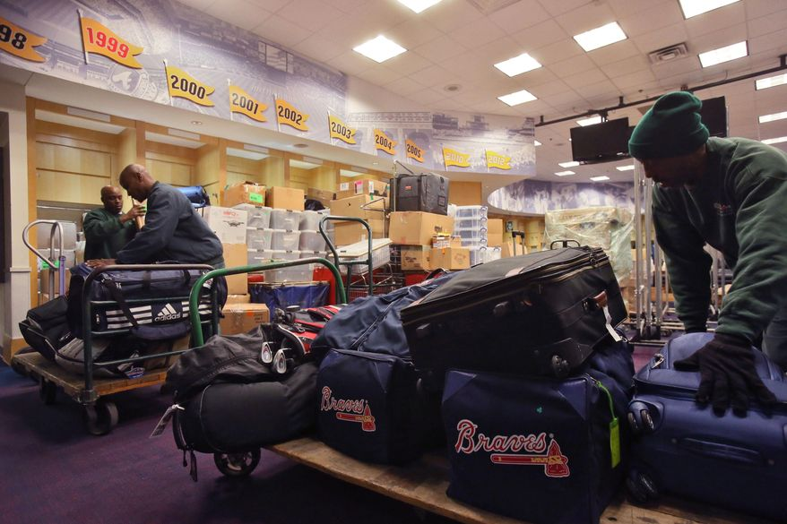 Workers from Atlanta Peach Movers helps pack and load Atlanta Braves baseball equipment for the trip south for spring training Friday, Feb. 7, 2014, in Atlanta. (AP Photo/Atlanta Journal-Constitution, Bob Andres)  MARIETTA DAILY OUT; GWINNETT DAILY POST OUT; LOCAL TV OUT; WXIA-TV OUT; WGCL-TV OUT