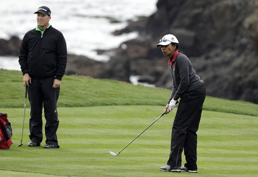 Former United States Secretary of State Condoleezza Rice, right, watches her ball roll up to the eighth green of the Pebble Beach Golf Links as playing partner D.A. Points, left, looks on during the second round of the AT&T Pebble Beach Pro-Am golf tournament on Friday, Feb. 7, 2014, in Pebble Beach, Calif. (AP Photo/Eric Risberg)