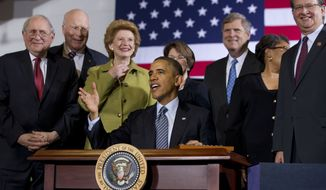 President Barack Obama, surrounded by members of Congress, looks up while signing the farm bill, Feb. 7, 2014, at Michigan State University in East Lansing, Mich. From left are, Sen. Carl Levin, D-Mich., Senate Agriculture Committee member Sen. Patrick Leahy, D-Vt. Senate Agriculture Committee Chair Sen. Debbie Stabenow, D-Mich., Senate Agriculture Committee member Sen. Amy Klobuchar, D-Minn., Agriculture Secretary Tom Vilsack, Rep. Marcia Fudge, D-Ohio and Rep. Gary Peters, D-Mich. (AP Photo/Jacquelyn Martin)