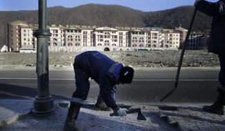 A construction worker removes paving bricks near hotel buildings on the opening day of the 2014 Winter Olympics, Friday, Feb. 7, 2014, in Krasnaya Polyana, Russia. (AP Photo/Jae C. Hong)