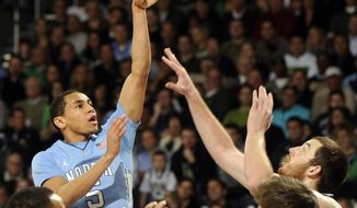 North Carolina guard Marcus Paige, left, puts up a shot over Notre Dame forward Garrick Sherman during the second half of an NCAA college basketball game Saturday, Feb. 8, 2014, in South Bend, Ind. (AP Photo/Joe Raymond)