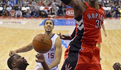 Toronto Raptors forward Terrence Ross, right, dunks as Los Angeles Clippers guard Reggie Bullock, lower left, defends and center Ryan Hollins watches during the first half of an NBA basketball game, Friday, Feb. 7, 2014, in Los Angeles. (AP Photo/Mark J. Terrill)