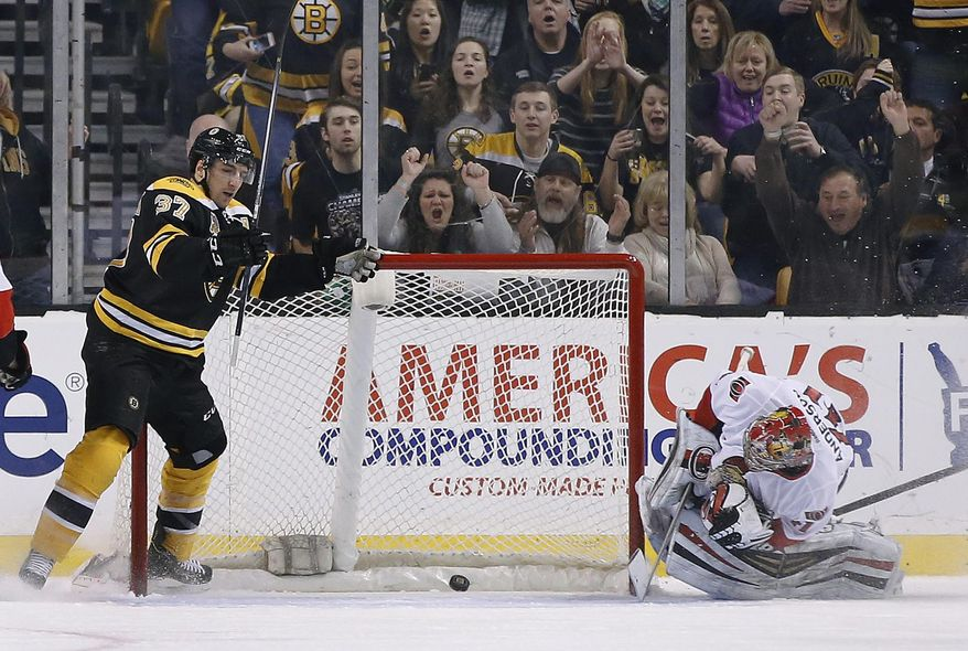 Boston Bruins center Patrice Bergeron (37) celebrates after scoring against Ottawa Senators goalie Craig Anderson (41) during the first period of an NHL hockey game in Boston, Saturday, Feb. 8, 2014. (AP Photo/Elise Amendola)