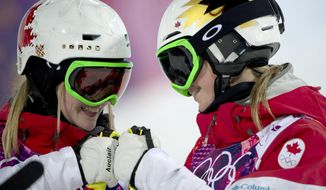 Canada's Justine Dufour-Lapointe, left, and Chloe Dufour-Lapointe bump fists as they are introduced for the women's moguls final at the Rosa Khutor Extreme Park, at the 2014 Sochio Winter Olympics, Saturday, Feb. 8, 2014, in Krasnaya Polyana, Russia. (AP Photo/The Canadian Press, Adrian Wyld)