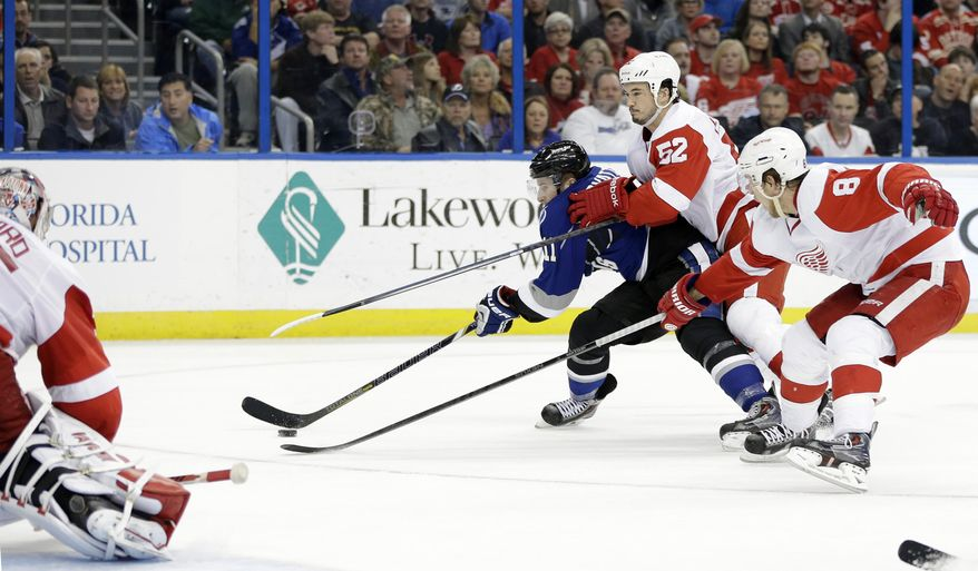 Tampa Bay Lightning center Tom Pyatt (11) gets past Detroit Red Wings defenseman Jonathan Ericsson (52) and left wing Justin Abdelkader (8) to score on goalie Jimmy Howard (35) during the second period of an NHL hockey game Saturday, Feb. 8, 2014, in Tampa, Fla. (AP Photo/Chris O'Meara)