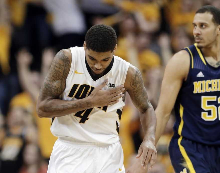 Iowa guard Devyn Marble, left, reacts in front of Michigan forward Jordan Morgan, right, after making a 3-point basket during the first half of an NCAA college basketball game, Saturday, Feb. 8, 2014, in Iowa City, Iowa. (AP Photo/Charlie Neibergall)