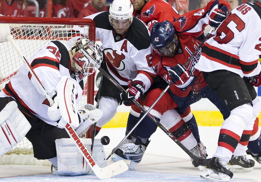 New Jersey Devils goalie Cory Schneider, left, and defenseman Andy Greene, second from left, defend against Washington Capitals right wing Joel Ward (42) during the second period of an NHL hockey game on Saturday, Feb. 8, 2014, in Washington. (AP Photo/ Evan Vucci)