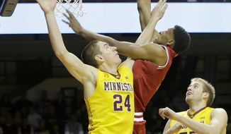 Indiana forward Troy Williams, center, is fouled by Minnesota forward Joey King (24) as Minnesota center Elliott Eliason (55) looks on during the first half of an NCAA college basketball game in Minneapolis, Saturday, Feb. 8, 2014. (AP Photo/Ann Heisenfelt)