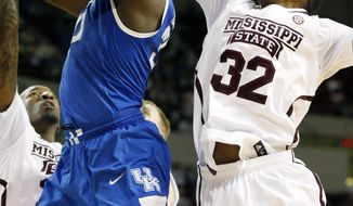 Mississippi State guard Craig Sword (32) knocks away the ball from Kentucky forward Julius Randle (30) in the second half of an NCAA college basketball game in Starkville, Miss., Saturday, Feb. 8, 2014. Kentucky won 69-59. (AP Photo/Rogelio V. Solis)