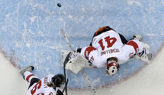 Tara Watchorn of Canada shoots past Julia Marty of Switzerland (6) and Goalkeeper Florence Schelling to score a goal in the first period of the women's ice hockey game at the Shayba Arena during the 2014 Winter Olympics, Saturday, Feb. 8, 2014, in Sochi, Russia. (AP Photo/Matt Slocum )