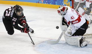 Goalkeeper Florence Schelling of Switzerland blocks Hayley Wickenheiser of Canada shot on the goal during the third period of the women's ice hockey game at the Shayba Arena during the 2014 Winter Olympics, Saturday, Feb. 8, 2014, in Sochi, Russia. (AP Photo/Petr David Josek)