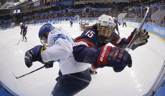 Nina Tikkinen of Finland and Anne Schleper of the United States battlers from control of the puck against the glass during the second period of the women's ice hockey game at the Shayba Arena during the 2014 Winter Olympics, Saturday, Feb. 8, 2014, in Sochi, Russia. (AP Photo/Matt Slocum)