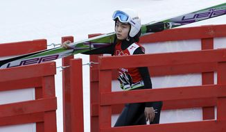 Japan's Sara Takanashi carries her skis during a women's ski jumping training session at the 2014 Winter Olympics, Saturday, Feb. 8, 2014, in Krasnaya Polyana, Russia. (AP Photo/Matthias Schrader)