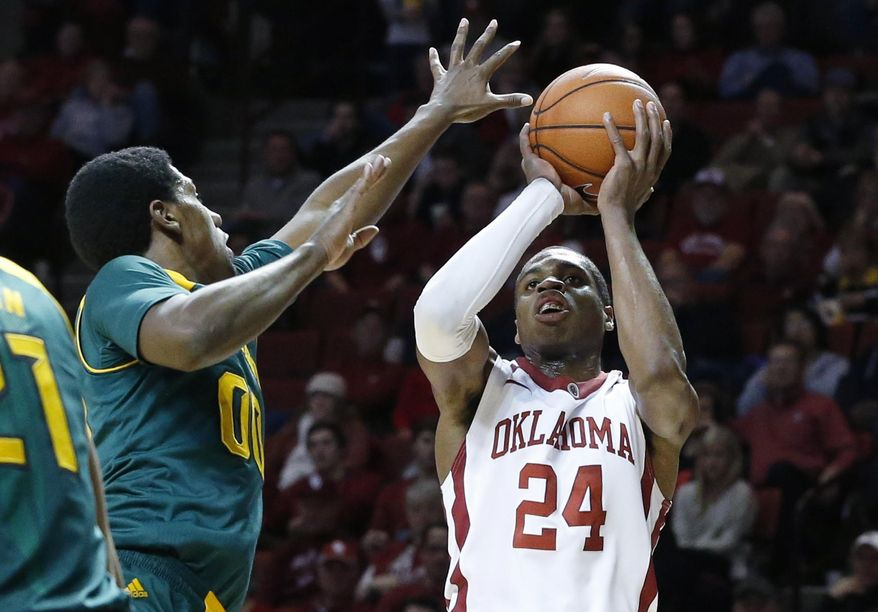 Oklahoma guard Buddy Hield (24) fakes a shot before passing to a teammate in front of Baylor forward Royce O'Neale (00) in the second half of an NCAA college basketball game in Norman, Okla., Saturday, Feb. 8, 2014. Oklahoma won 88-72. (AP Photo/Sue Ogrocki)