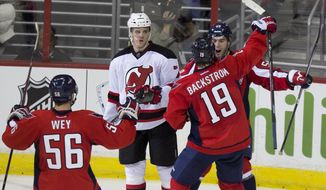 New Jersey Devils defenseman Mark Fayne, second from left, looks on as Washington Capitals defenseman Julien Brouillette, right, is congratulated by teammates Patrick Wey, left, and Nicklas Backstrom after scoring the go-ahead goal during the third period of an NHL hockey game on Saturday, Feb. 8, 2014, in Washington. The Capitals defeated the Devils 3-0. (AP Photo/ Evan Vucci)