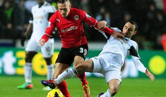 Swansea's Leon Britton, right, competes for the ball with Cardiff's Craig Bellamy during the English Premier League soccer match between Swansea City and Cardiff City at the Liberty Stadium, Swansea, Wales, Saturday, Feb. 8, 2014.  (AP Photo/Rui Vieira)