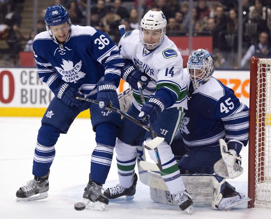 Toronto Maple Leafs defenseman Carl Gunnarsson (36) and Vancouver Canucks right winger Alexandre Burrows (14) battle for the puck in front of goaltender Jonathan Bernier during the first period of an NHL hockey game, Saturday, Feb. 8, 2014 in Toronto. (AP Photo/The Canadian Press, Frank Gunn)