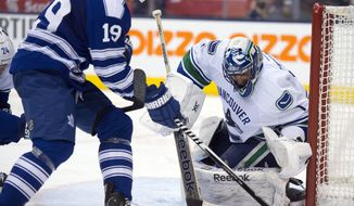 Vancouver Canucks goaltender Roberto Luongo makes a save on Toronto Maple Leafs left winger Joffrey Lupul during the second period of an NHL hockey game, Saturday, Feb. 8, 2014 in Toronto. (AP Photo/The Canadian Press, Frank Gunn)