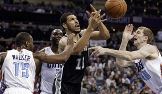 San Antonio Spurs' Jeff Ayres (11) is fouled as he drives between Charlotte Bobcats' Kemba Walker (15) and Cody Zeller (40) during the first half of an NBA basketball game in Charlotte, N.C., Saturday, Feb. 8, 2014. (AP Photo/Chuck Burton)