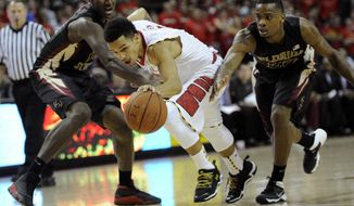 Maryland guard Seth Allen, center, drives to the basket between Florida State forward Robert Gilchrist, left, and Aaron Thomas, right, during the second half of an NCAA college basketball game on Saturday, Feb. 8, 2014, in College Park, Md. Maryland won 83-71. (AP Photo/Nick Wass)