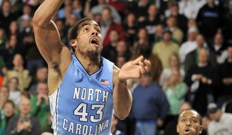 North Carolina forward James McAdoo puts up a shot as he collides with Notre Dame forward Zach Auguste during the second half of an NCAA college basketball game Saturday, Feb. 8, 2014, in South Bend, Ind. (AP Photo/Joe Raymond)