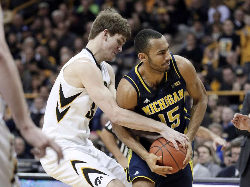 Iowa center Adam Woodbury, left, tries to steal the ball from Michigan forward Jon Horford during the first half of an NCAA college basketball game, Saturday, Feb. 8, 2014, in Iowa City, Iowa. (AP Photo/Charlie Neibergall)