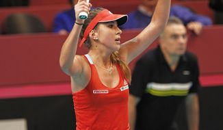 Switzerland's Belinda Bencic rasies her arms after winning her match against France's Alize Cornet, during the Fed Cup match between France and Switzerland, at the Coubertin stadium in Paris, Saturday Feb. 8, 2014. (AP Photo/Remy de la Mauviniere)